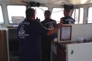 View from within the deckhouse looking towards the captain's chair looking at the back of Captain Steve and 3 guys from Atlantic Service & Equipment with their branded t-shirts on