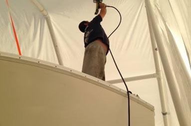 Joe, from Atlantic Service and Equipment were the boat is being worked on, uses a hand held dryer to smooth out the tent