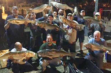 Night group shot back at the marina of everyone holding their catch