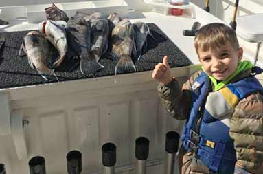 Still on the boat, back at the dock, a young boy smiles and gives a thumbs up standing next to a spread of striped bass on the fillet table.