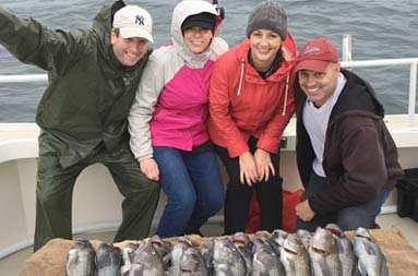 Group photo of two women and two men standing behind a spread of sea bass and smiling for the camera.
