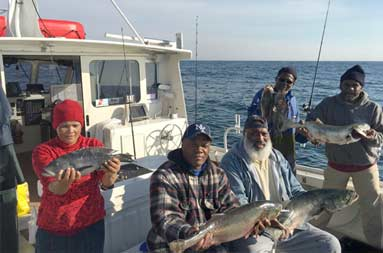 Five men on the boat proudly show off the their catch.