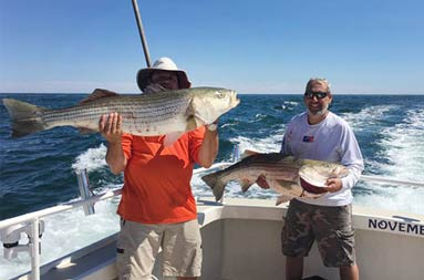 Two men smile and proudly hold up the striped bass they each caught.