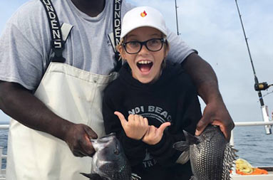 First mate, Gil, holds up the line with 2 sea bass, and the young boy who caught them has a very excited smile on his face as he points to the fish on either side of him with his thumbs.