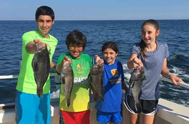 An adolescent boy and girl, along with a younger boy and girl each smile and hold out the sea bass they caught for the camera.