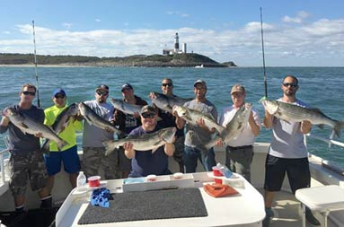 With the Montauk lighthouse, along with a blue sky and clouds in the background, 9 men smile and each hold up the striped bass they caught.