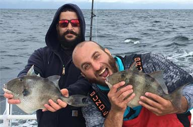 Two men each hold up the trigger fish they caught. One pretends to be eating it.