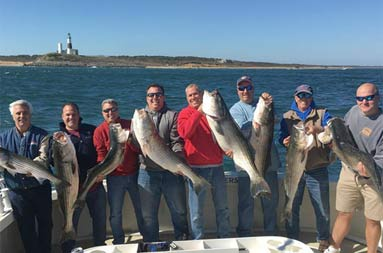 With a clear blue sky and the lighthouse in the background, 8 men smile and proudly hold up their striped bass.
