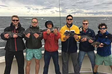 Six men standing on the boat, each holding out the sea bass they caught.