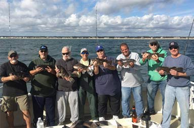 Eight men each hold up 1 blackfish (tautog).
