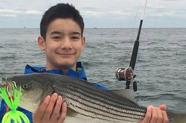 An adolescent boy wearing a blue jacket smiles as he holds up his striped bass with 2 hands.