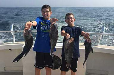 Two adolescent boys smile big and hold up two sea bass each