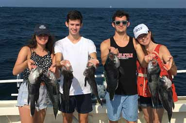 A group of 2 men and 2 women each hold up 2 sea bass.