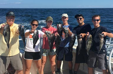 A man, 2 teenage women and 3 teenage men each hold up 2 sea bass and smile for the camera