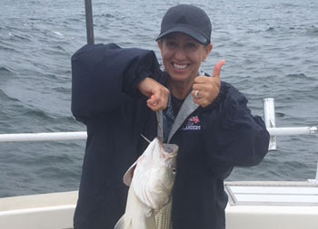 A woman wearing a blue jacket and baseball cap, gives a thumbs up to the camera as she holds up her striped bass with the other hand.