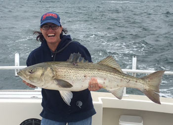 A woman gives a big smile as she holds up a striped bass with two hands.