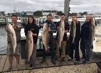A group of six men stand in a group on the dock, and each holds up the striped bass they caught.