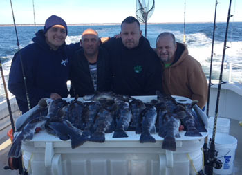 A group of 4 men outfitted in sweatshirts and hats, stand around the filet table where their catch of blackfish is displayed.