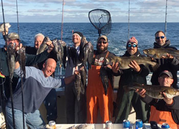 On a cold fall day on the water, a group of 8 men smile for the camera and hold up the fish they caught.